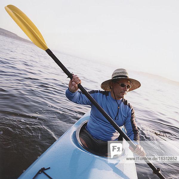 Mann Seekajakfahren in der Dämmerung