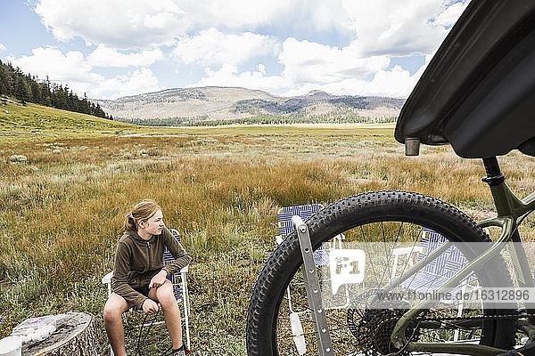 Ein jugendliches Mädchen sitzt in einer offenen Landschaft und bereitet sich auf eine Fahrradtour vor.