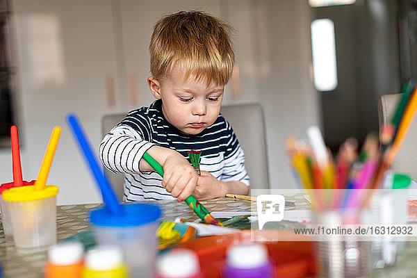 Dreijähriger Junge  der zu Hause mit Töpfen und Pinseln malt.