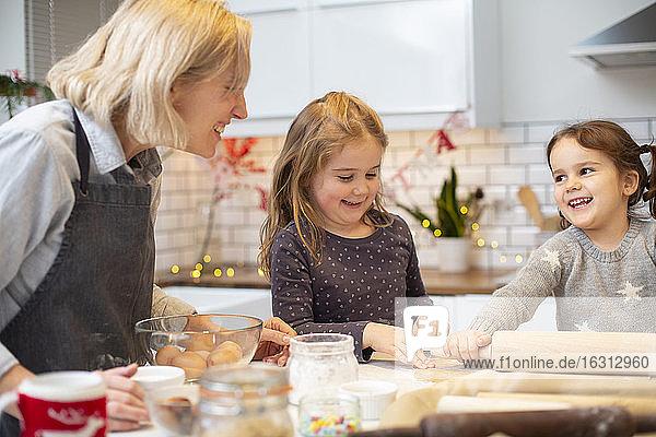 Blonde Frau mit blauer Schürze und zwei Mädchen stehen in der Küche und backen Weihnachtsplätzchen.