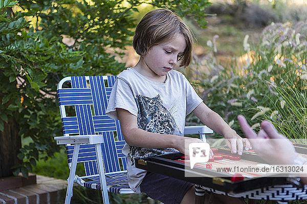 Ein kleiner Junge spielt Backgammon im Freien in einem Garten.