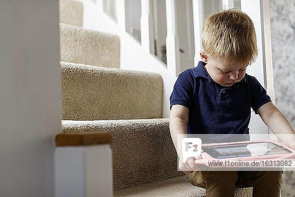 Ein dreijähriger Junge saß auf der Treppe und betrachtete ein digitales Tablett.