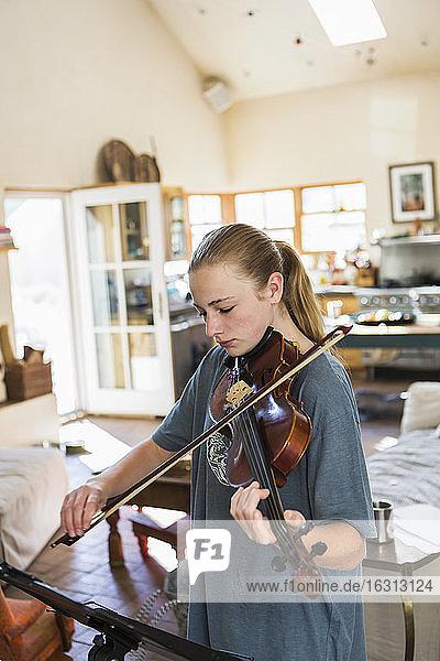 Teenagerin spielt zu Hause Geige