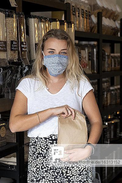 Frau mit Gesichtsmaske kauft ein und füllt eine Papiertüte mit losen Zutaten
