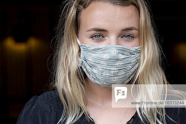Bildnis einer jungen blonden Frau mit blauer Gesichtsmaske.