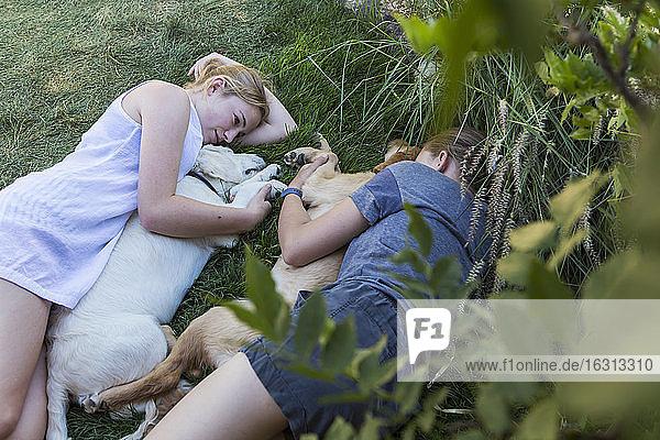 Zwei Mädchen im Teenager-Alter liegen auf dem Rasen und umarmen ihre Golden Retriever-Hunde.