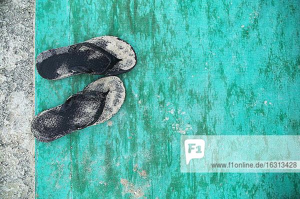 Hochwinkel-Nahaufnahme von sandig-schwarzen Flip-Flops auf türkisfarbener Bodenmatte.