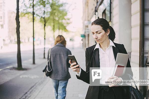 Geschäftsfrau benutzt Mobiltelefon in der Stadt