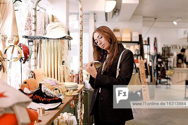 Junge Frau betrachtet Schüssel im Einzelhandel
