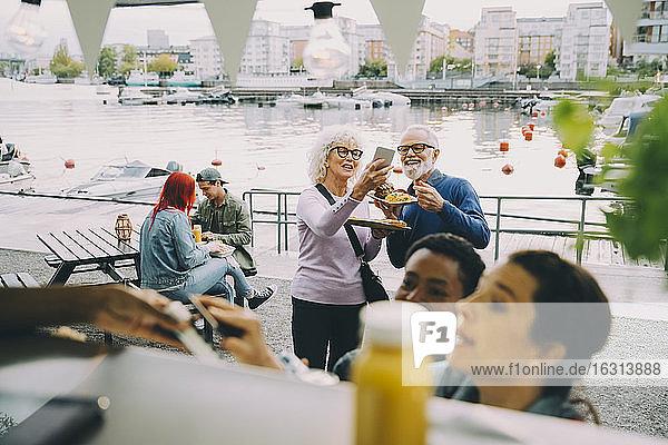 Lächelnder älterer Mann und lächelnde ältere Frau  die sich inmitten von Kunden mit einem Imbisswagen selbstständig machen