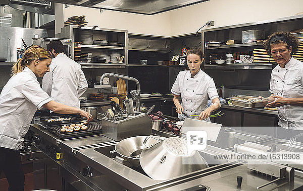 Chefs preparing food in commercial kitchen at restaurant