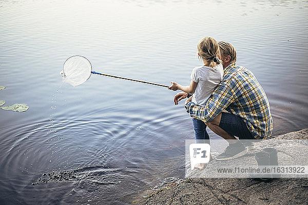 Hochwinkelaufnahme von Vater und Tochter beim Angeln im See