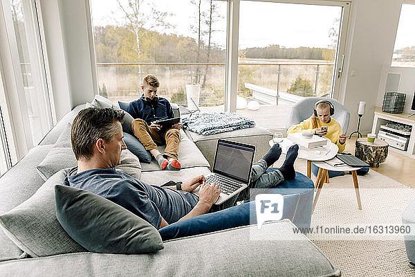 Hochwinkelansicht von Vater und Kindern mit drahtloser Technologie zu Hause