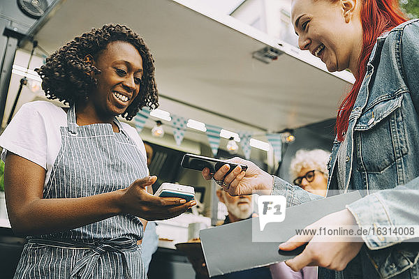 Niedriger Blickwinkel auf einen Kunden  der in der Stadt über ein Smartphone bezahlt