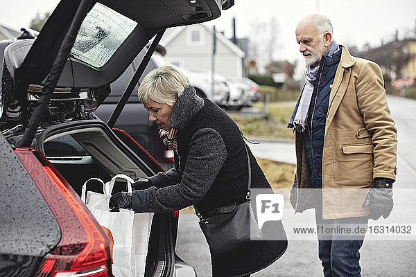 Älterer Mann schaut auf Partner  der im Winter am Kofferraum des Autos steht