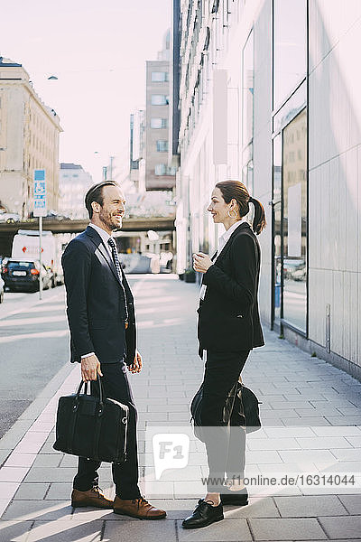 Side view of business people standing on sidewalk