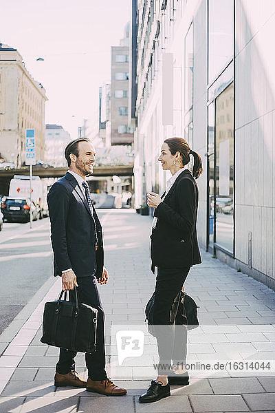Seitenansicht von Geschäftsleuten  die auf dem Bürgersteig stehen