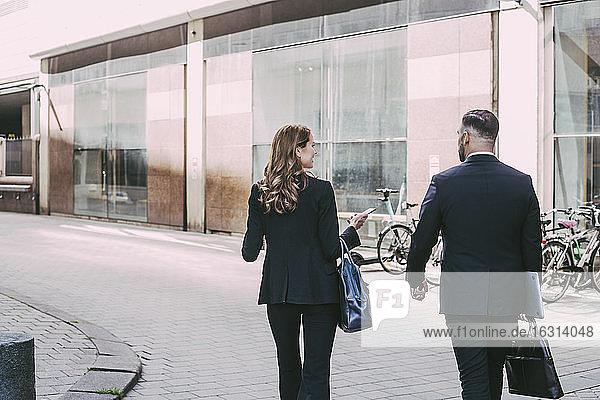 Rückansicht einer Geschäftsfrau und eines Geschäftsmannes  die in der Stadt spazieren gehen
