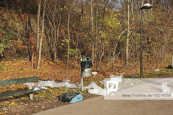 Hochwinkelaufnahme von Plastikmüll  der im Herbst im Park von einer Bank verstreut wurde