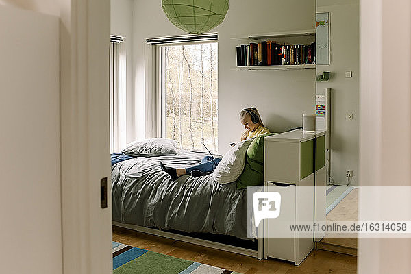 Mädchen in voller Länge  das ein Smartphone benutzt  während es im Schlafzimmer sitzt und durch die Tür gesehen wird