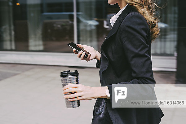Mitten in der Stadt: Geschäftsfrau mit Kaffeetasse und Telefon