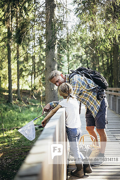 Father with backpack talking to daughter on footbridge in forest