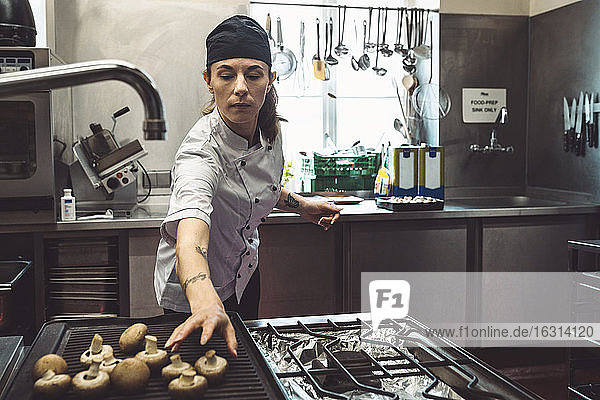 Female chef arranging mushrooms on barbecue grill in commercial kitchen