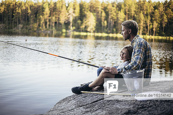Portrait of smiling daughter fishing with father while sitting by lake