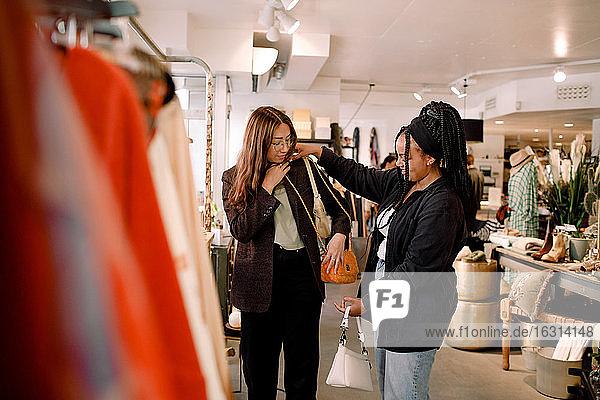 Smiling women shopping bags at retail store