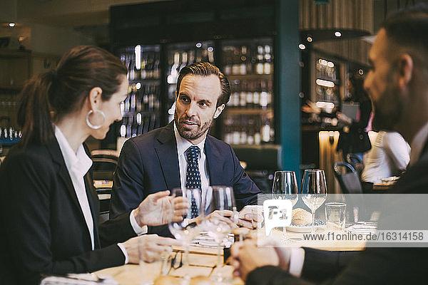 Confident businessman talking to businesswoman in restaurant