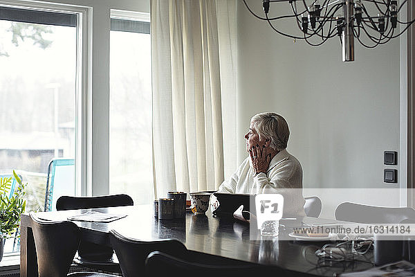 Senior woman looking away while sitting by dining table at home