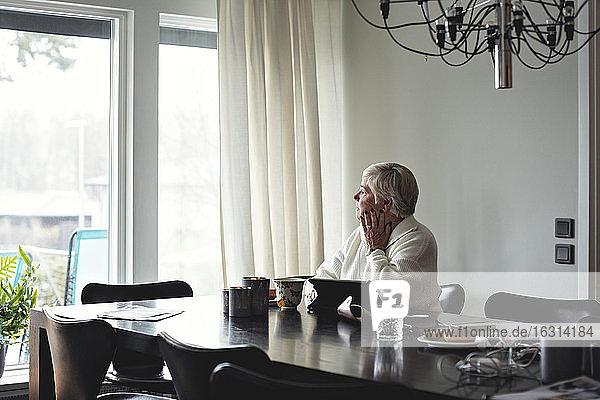 Ältere Frau schaut weg  während sie zu Hause am Esstisch sitzt