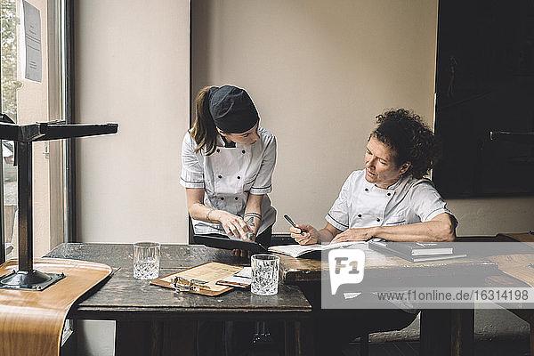 Köchinnen diskutieren am Tisch im Restaurant