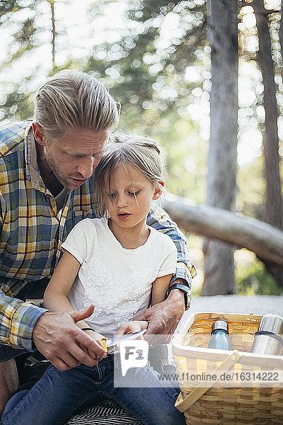 Vater hilft Tochter beim Stockschneiden mit Messer im Wald