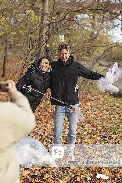 Junge Umweltschützerin fotografiert lächelnde Freunde  die im Park Mikroplastik halten