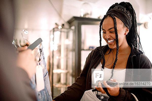 Freundin zeigt lächelnder Frau im Modegeschäft Kleider