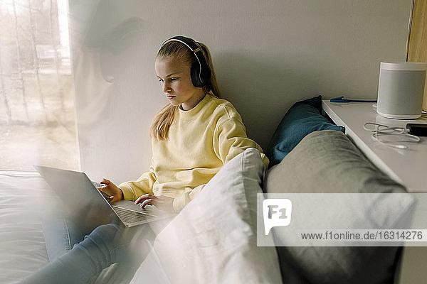 Mädchen mit Kopfhörern am Laptop  während sie auf dem Bett sitzt