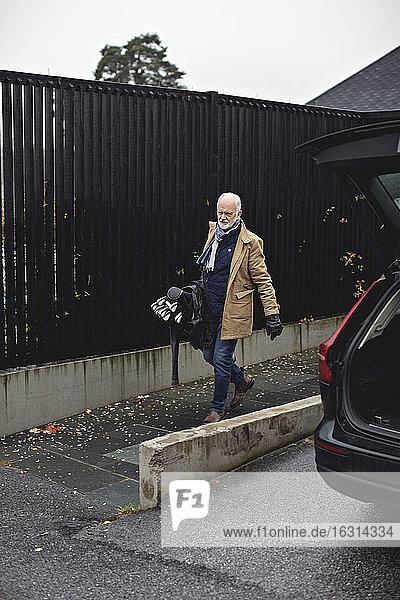 Senior man with golf bag walking on sidewalk during winter