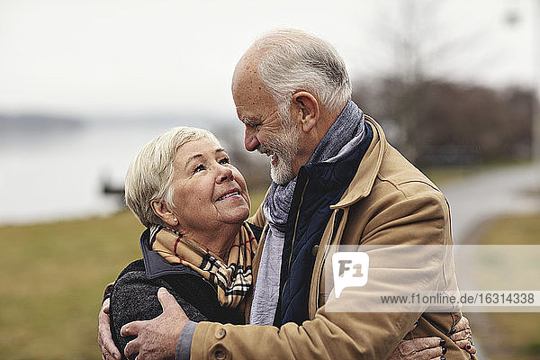 Smiling senior couple embracing each other by lake
