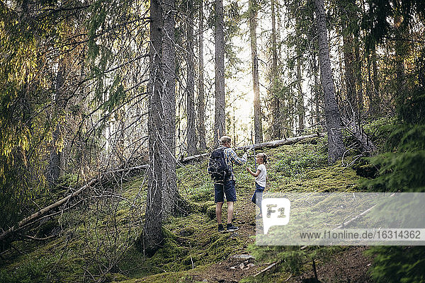 Father with backpack talking to daughter in forest