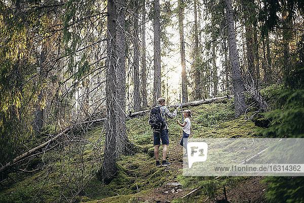 Vater mit Rucksack spricht mit Tochter im Wald