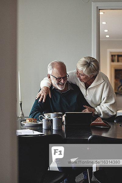 Lächelndes älteres Paar beim Gespräch am Esstisch im Wohnzimmer