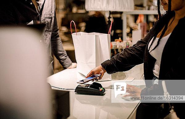 Mittlerer Teil der Kundin  die im Geschäft per Smartphone bezahlt