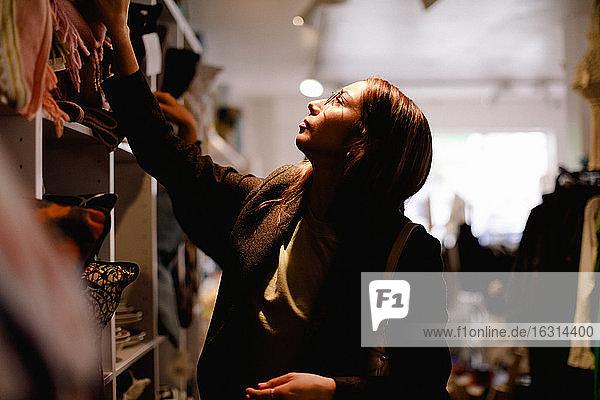 Junge Frau schaut beim Einkaufen im Einzelhandelsgeschäft auf