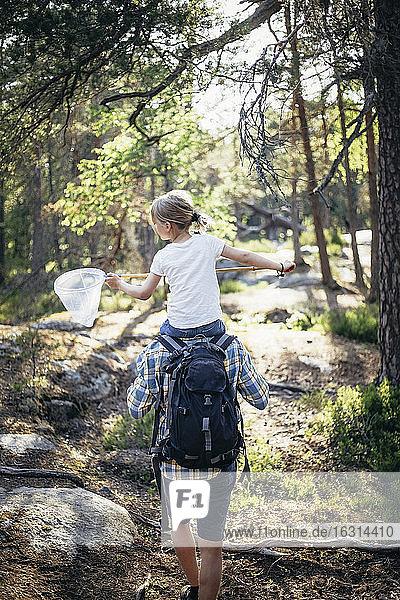 Rückansicht eines Vaters  der seine Tochter auf der Schulter im Wald trägt