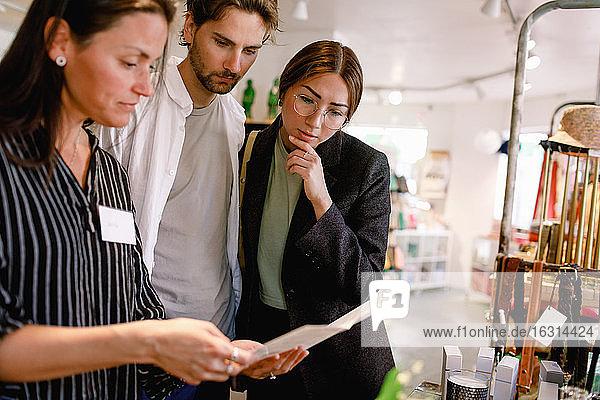 Verkäuferin zeigt dem Paar im Modegeschäft eine Broschüre