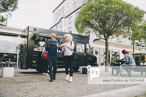 Senior male and female customers with street food walking against commercial land vehicle in city