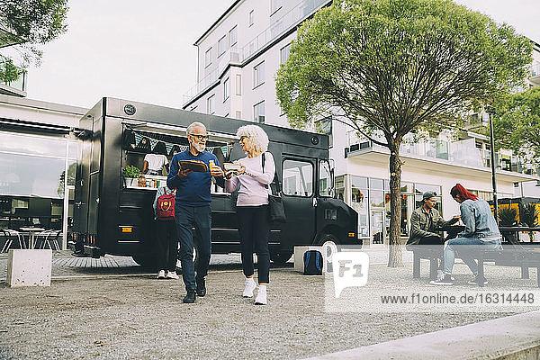 Ältere männliche und weibliche Kunden mit Straßenessen  die in der Stadt gegen ein Nutzfahrzeug laufen