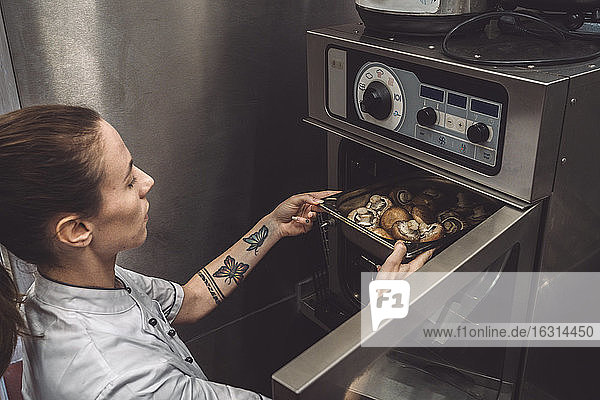High angle view of female chef baking mushrooms in oven