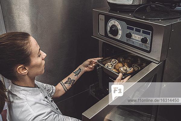 Hochwinkelansicht einer Köchin beim Backen von Pilzen im Ofen